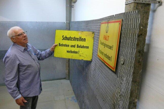 <p>In einer bereits gestalteten Ecke des Museums, die sich Deutschlands Teilung widmet, präsentiert Arnulf Teuchert ein historisches Schild. Auch original NVA-Stacheldraht, Pfosten und Zäune aus der Schutzzone sind dort zu sehen.</p>