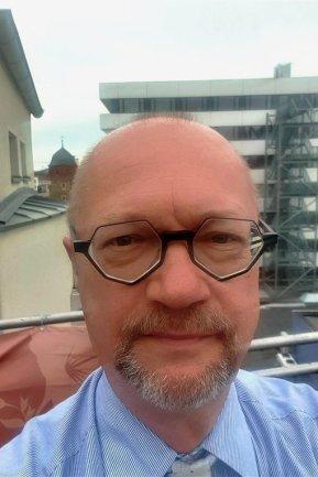 """<p>Dietmar Bartel, Jahrgang 1962, ist der Chef vom Dienst. Damit ist er redaktionelle Schnittstelle zu Produktionsplanung, Anzeigenabteilung, Druckzentrum und Technik. Bei ihm landen alle Honorarabrechnungen zur Unterschrift und manche Anfrage von Kollegen, bei denen er ihre """"letzte Rettung"""" ist. Insgesamt versteht er sich deshalb vor allem als Dienstleister für seine Kollegen.</p>"""