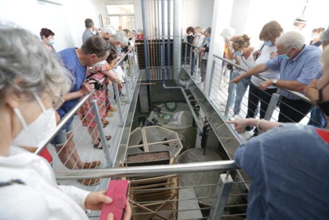 <p>Besucher beugen sich gespannt über das Geländer: Im Keller des Aquaponikturms stehen die Fischtanks.</p>
