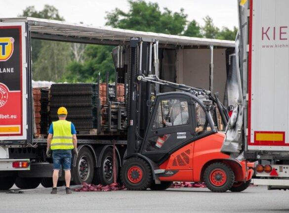 <p>Verladen von Dachziegeln auf einen LKW.</p>