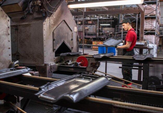 <p>Ein Mitarbeiter kontrolliert die Oberfläche eines engobierten Dachziegels.</p>