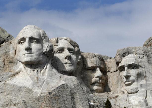 <p>Gleiche mehrere Männer drängeln ihre Köpfe im Mount Rushmore gegeneinander. Die Porträtköpfe zeigen die Ex-Präsidenten George Washington (v.l.n.r.) Thomas Jefferson, Theodore Roosevelt und Abraham Lincoln.</p>