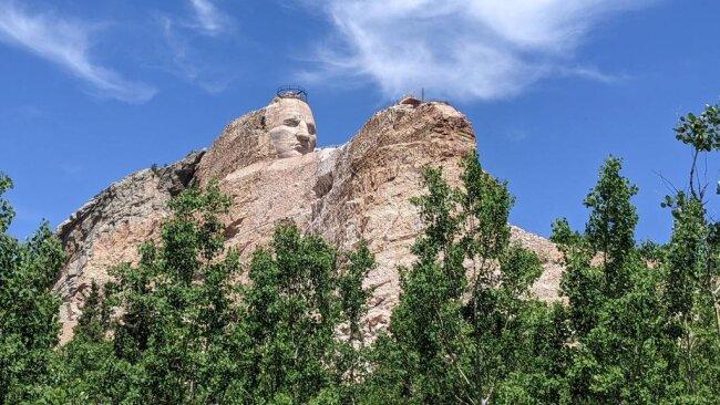 <p>Die Crazy Horse Skultpur zu Ehren der amerikanischen Uhreinwohner liegt nur 14 Kilometer vom Mount Rushmore entfernt. Sie ist noch nicht fertiggestellt, soll am Ende aber bescheidene 195 Meter lang und 172 Meter hoch sein.</p>