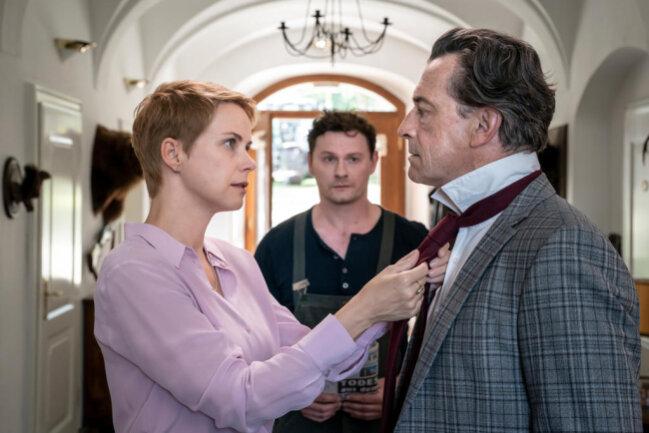 <p>Agnes Huber (Andrea Osvárt, l.) bindet ihrem Mann, dem Großbauern Arnold Huber (Thomas Sarbacher, r.) die Krawatte. Vorarbeiter Sebastian Kreuzig (Shenja Lacher, M.) schaut zu.</p>