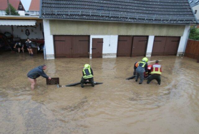 Helfer und Feuerwehrleute standen auf dem Hof an der Bachstraße am Samstag teilweise kniehoch in der braunen Brühe.