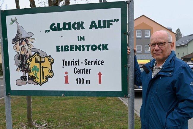 """An den Ortseingängen von Eibenstock stehen Schilder - Wurzelrudi und ein """"Glück auf"""" grüßen die Gäste. Thomas Maixner, hier am Ortseingangsschild von Eibenstock, genügt das nicht. Er hätte gern, dass der traditionelle Gruß aus dem Erzgebirge im Alltag mehr genutzt wird."""