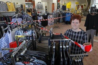 Pascaline Löscher, Inhaberin des Modegeschäfts Bru-He in Wilkau Haßlau, darf keine Kunden mehr in ihren Laden lassen, obwohl die Frühlingskleidung eingetroffen ist. Nur die Post-Agentur (hinten) bleibt offen.