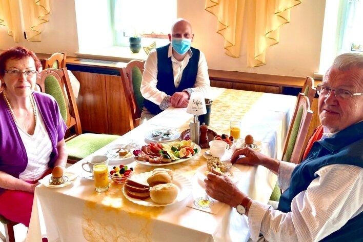 """Ingrid Hujer und Hartmut Gerhardt machen Urlaub im Hotel """"Schwarzes Ross"""". Inhaber Maik Heiden (hinten) liegt das Covid-Ex-Projekt Oberwiesenthal sehr am Herzen."""