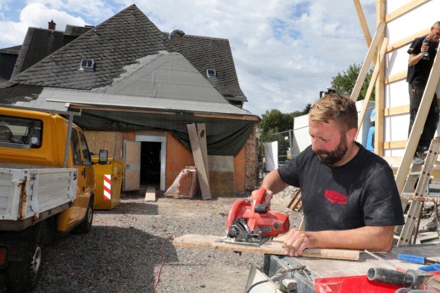 Mario Kunze (vorn) und Stev Meyer vom Baugeschäft Hegenbart aus Gablenz stellten am Dienstag die Bautafel im Gelände des Hauses der Vereine auf. Wo sie hier arbeiten, stand bis 2019 der Kegelbahn-Anbau.