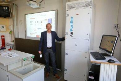 Volker Bilz, Chef der Glauchauer Berufsförderung, zeigt den neuen Luftreiniger. In jedem Klassenraum der Achatschule steht so ein Gerät.