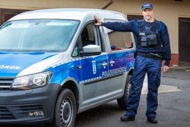 Thomas Karl mit seinem Dienstfahrzeug, einem VW Caddy, der mit Spezialfolie ein Polizei-ähnliches Design verpasst bekommen hat.
