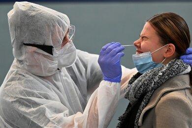Ein Helfer nimmt bei einer Schülerin eine Probe für einen Corona-Schnelltest.