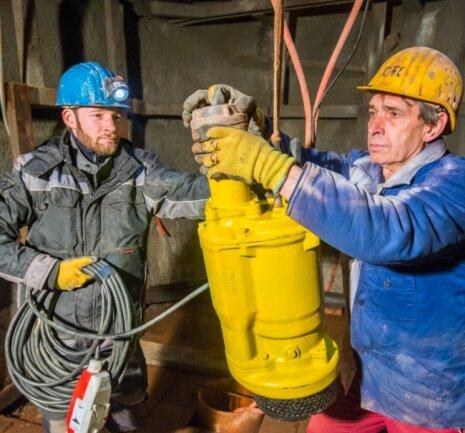 Manuel Schönherr (links) und Uwe Trommler sind in 14 Meter Tiefe im Johannes-Schacht dabei, die Wasserpumpe einzusetzen.