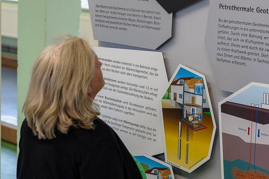 """Kispileiterin Maria Faldum vor einem der Plakate in der Ausstellung """"Sachsen hebt seine Schätze"""". Geophysiker Gerd Wolf weist darauf hin, dass Tiefengeothermie und Geothermie unterschiedliche Verfahren sind."""