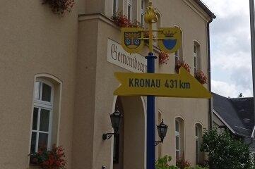 Ein Wegweiser vorm Hohndorfer Rathaus. Auch in der Partnerstadt wird auf diese Weise auf Hohndorf verwiesen.