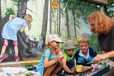 Mathilda, die für das Mädchen auf dem Bild Modell stand, und ihre Freunde Nevio und Vasco (von links) durften Dirk Söllner über die Schulter schauen und sich erklären lassen, wie Farben gemischt werden.