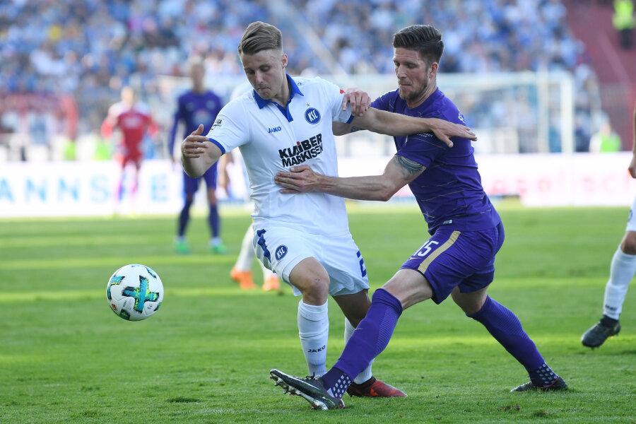 Der Karlsruher Marco Thiede (links) und der Auer Dennis Kempe kämpfen um den Ball.