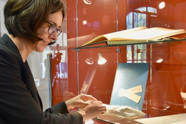 Esche-Museumsleiterin Barbara Wiegand-Stempel richtet eine Vitrine der Sonderschau über Oberfrohnas Historie ein, die auch Handschuhe aus der Firma Hermann Dittrich auf der Frohnbachstraße zeigt.
