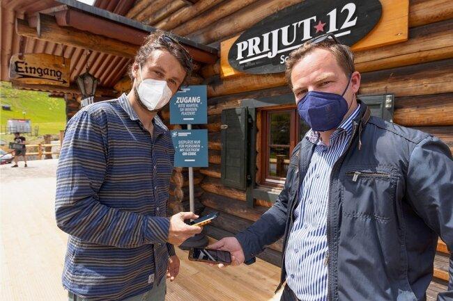 """Philipp Heinrich, Inhaber des Restaurants """"Prijut 12"""", und Covid-Exit-Projektmanager Erik Schulze (v. l.) demonstrieren, dass im einfachsten Fall ein Smartphone genügt, um sich registrieren zu lassen."""