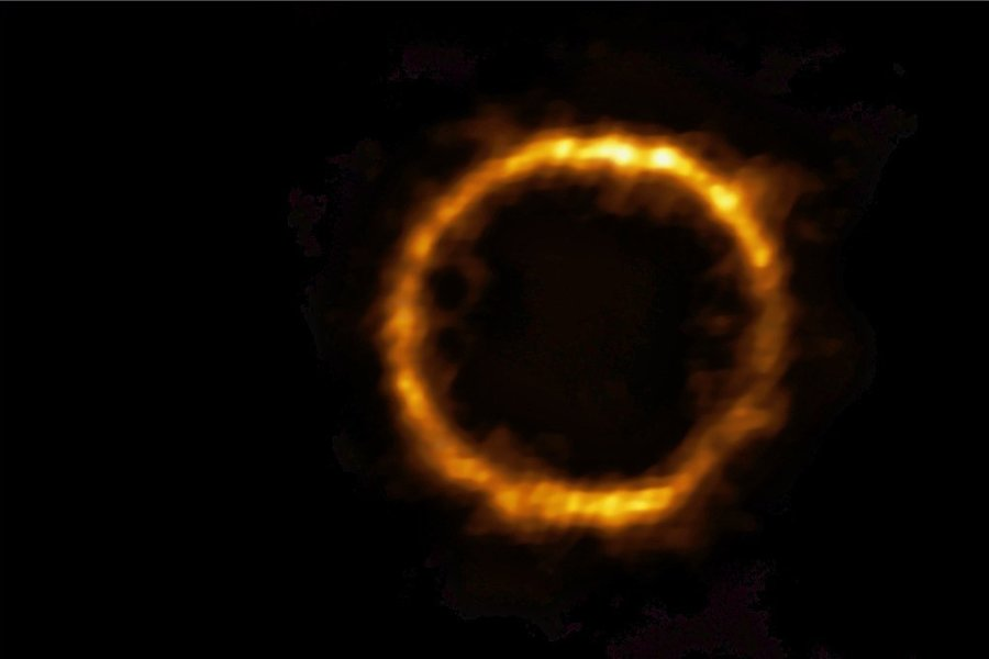 Sieht aus wie eine ringförmige Sonnenfinsternis, ist es aber nicht. So sieht das Licht einer Galaxis kurz nach dem Urknall aus.