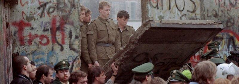 """<p class=""""artikelinhalt"""">11. November '89. Grenzsoldaten sehen zu, wie Demonstranten eines der ersten Segmente am Brandenburger Tor niederreißen. </p>"""