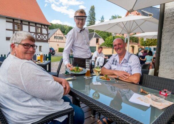 Hotelfachmann Yannick Ihle trägt Gesichtsschutz, wenn er im Restaurant des Hotels Saigerhütte Gäste wie Silvia und Gerd Schmitz bedient.