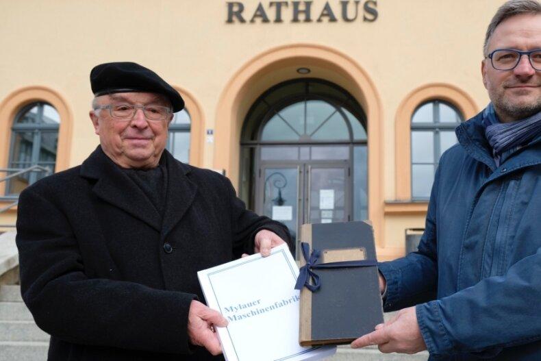 Günter Hofmann, Urenkel des Firmengründers Ferdinand Hofmann, übergibt die Dokumentation an Reichenbachs OB Raphael Kürzinger (rechts). Mit ins Stadtarchiv geht auch ein originales Lieferbuch der Firma.