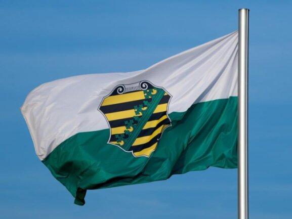 Die Flagge vom Bundesland Sachsen mit dem sächsischen Wappen weht im Wind.