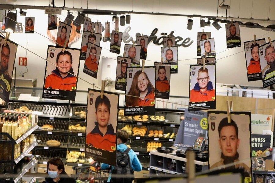 Ein 50 Meter lange Girlande mit den Fotos von Feuerwehrfrauen und -männern zieht sich durch den Markt.