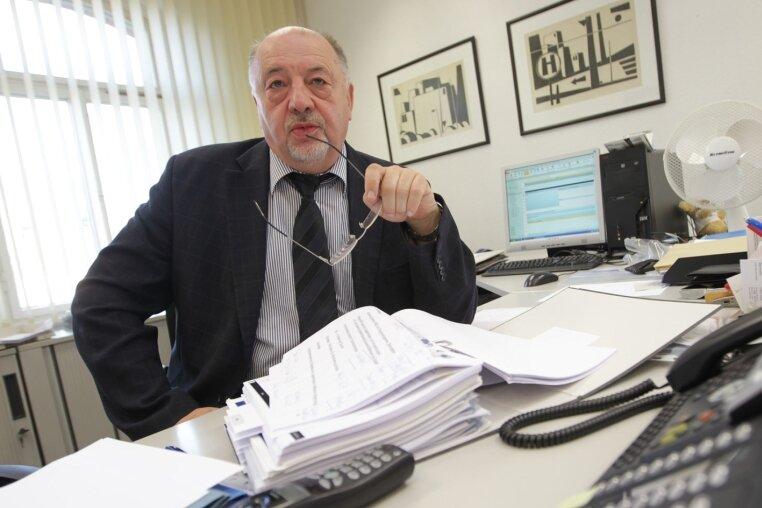 Hellfried Unglaub in typischer Pose an seinem Schreibtisch. Wenn er zu laut beschimpft wird, bietet er gerne ein Glas Milch an.
