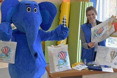 Sozialpädagogin Svenja Brandenburger und Elefant Kibu packen die Familien-Mutmach-Taschen im Familienzentrum.