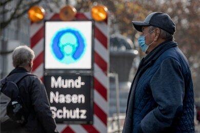 Szene aus einer Fußgängerzone am Wochenende in Dortmund: Eine LED-Tafel für Baustellen dient als Hinweisschild für das Tragen des Mund-Nasen-Schutzes. Die Pandemielage bleibt angespannt.