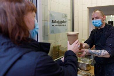 Koch Robert Grun reicht an dem neuen Abholschalter in Pörschis Kantine zwei Portionen Pasta mit Soße heraus. Um weniger Plastikmüll zu verursachen, wird das Essen zum Mitnehmen in ökologischen Bechern ausgegeben.