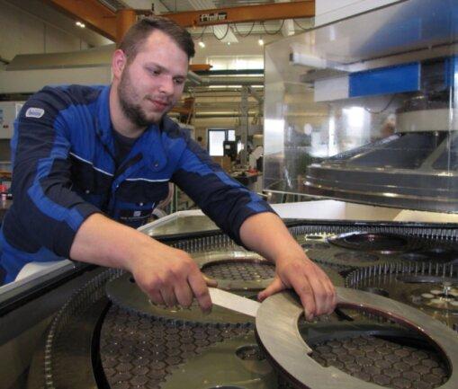 Felix Jendrosek, technischer Auszubildender im dritten Lehrjahr, steht an der nagelneuen Feinschleifmaschine und entnimmt die fertigen Rundmesser.