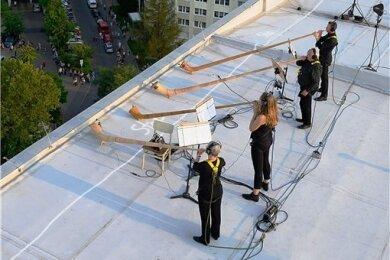 """Musiker der Dresdner Sinfoniker stehen mit Gurten gesichert während des Konzerts """"Himmel über Prohlis"""" auf dem Dach eines Hochhauses im Dresdner Stadtteil Prohlis."""