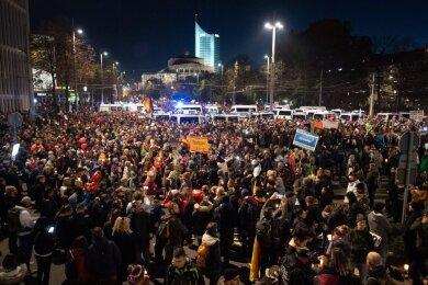 Teilnehmer stehen nach der Demo umgeben von Einsatzfahrzeugen der Polizei am Leipziger Hauptbahnhof.