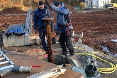 Mitarbeiter eine Brunnenbau -und Sanierungsfirma aus Hof legen den Brunnen frei.