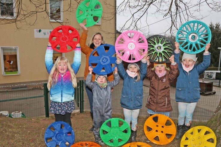 """Die Mädchen und Jungen in der Kita """"Happy Kids"""" und Leiterin Daniela Aßmann sind glücklich: Die zu Blumen umfunktionierten Radkappen, die im Sommer gestohlen worden waren, sind wieder da."""