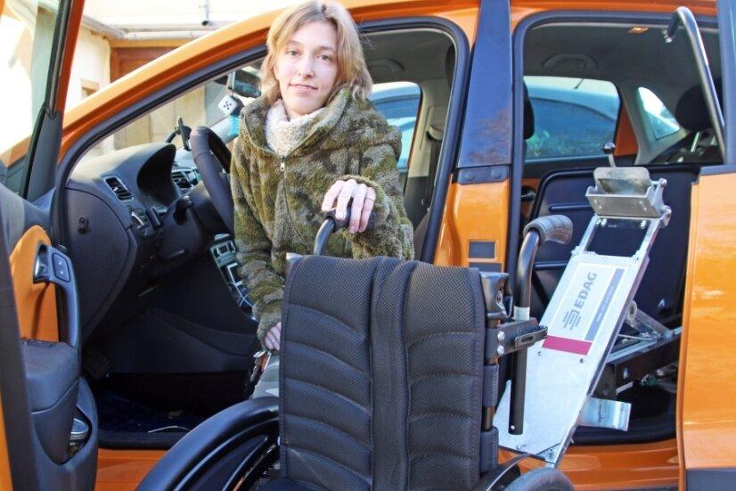 Sandra Hauptmann mit ihrem Auto, das für sie zu tief und für ihren Rollstuhl zu klein ist.