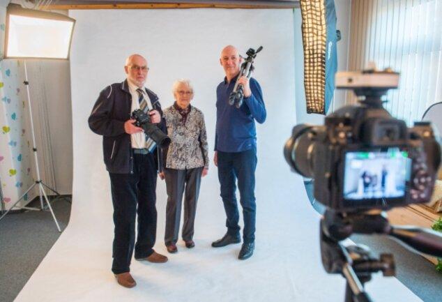 Für dieses Familienporträt haben sie ausnahmsweise einmal vor der Kamera Aufstellung genommen: Rudolf Martin (links, hier mit einer japanischen Rollfilmkamera von Mamiya aus den 1980er-Jahren samt Zeiss-Teleobjektiv). Er hat das Geschäft zusammen mit seiner Frau Christine (Mitte) jahrzehntelang geleitet. Heute steht sein Sohn Frank (rechts) alleine im Laden, am Drucker und hinter der Studiokamera.