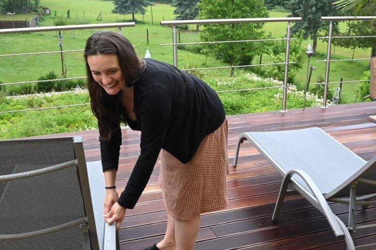Daniela Schönherr auf dem Balkon des Wohnhauses mit zwei Ferienwohnungen. Besucher blicken ins Chemnitztal.