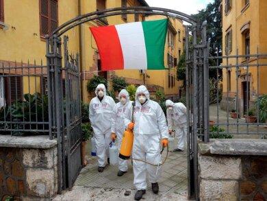 Arbeiter in Schutzkleidung desinfizieren Gehwege in Rom.