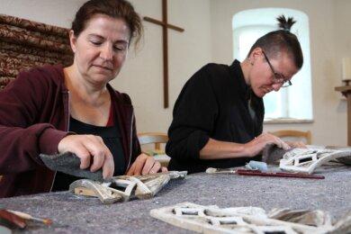 Die Malerinnen Manuela König-Schilbach (links) aus Plauen und Tanja Pohl aus Greiz verrichten filigrane handwerkliche Arbeiten an den Schnitzereien der Orgel.