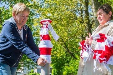 Gabriela Blechschmidt und Renate Müller (rechts) ziehen einem Poller eine rot-weiß geringelte Mütze an.