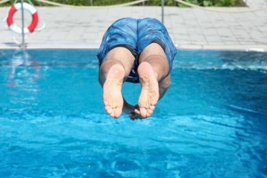 Ein Mann springt von einem Sprungbrett kopfüber ins Wasser.
