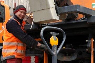 Mirko Georgi vom Stadtbauhof baut am Heck eines Fahrzeugs das Gegengewicht ab, das wegen des jetzt montierten Streuaufsatzes nicht gebraucht wird.