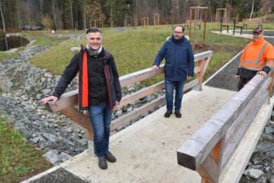 Freuen sich auf die Freigabe am 22. Dezember: Bürgermeister Olaf Schlott (Unabhängige Bürgerschaft), Planer Jens Möller und Bauhofchef Andreas Porkert (von links). Sie stehen auf der Brücke des freigelegten Kellergrundbaches.