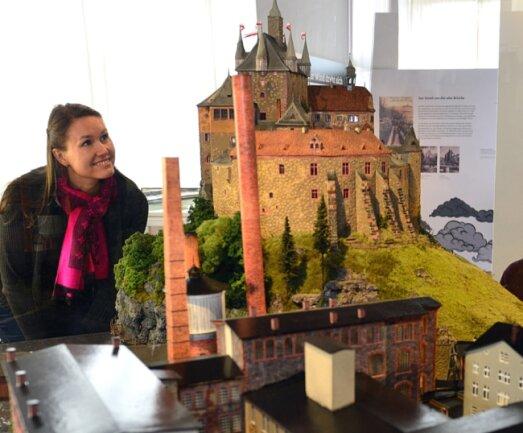 """Burgverwalterin Susanne Tiesler in der aktuellen Ausstellung """"Dicke Luft. Burg Kriebstein und die Papierfabrik 1856-1945"""",hier das von Andreas Funke gebaute Modell."""