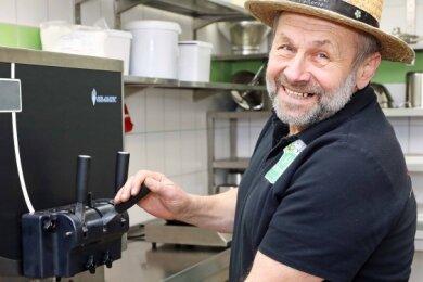 Ingo Weber, der mit seinem Sohn die Hofmolkerei Pleißental betreibt, füllt die 230-Milliliter-Becher mit der Eismischung ab.