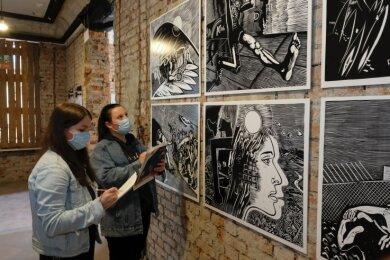 Celina Müller (links) und Josephine Zimmermann betrachten Grafik-Repliken des Künstlers Wolfgang Mattheuer im Haus Solbrigplatz 1.